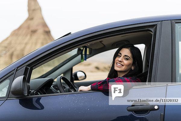 Spanien  Navarra  Bardenas Reales  glückliche junge Frau  die aus dem Autofenster schaut