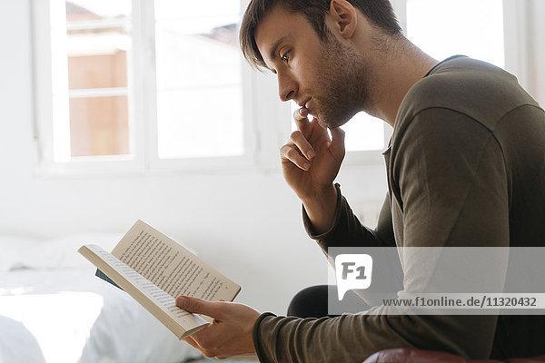 Junger Mann beim Lesen zu Hause