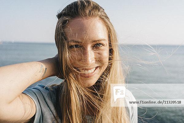 Porträt einer glücklichen jungen Frau mit blasenden Haaren vor dem Meer