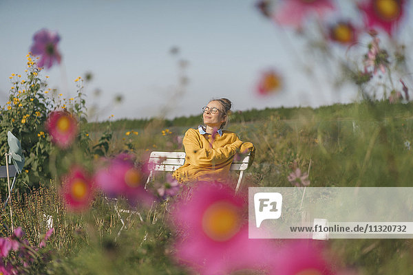 Junge Frau entspannt sich im Hausgarten