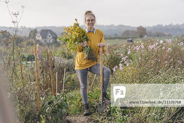 Lächelnde junge Frau hält Pflanze im Bauerngarten