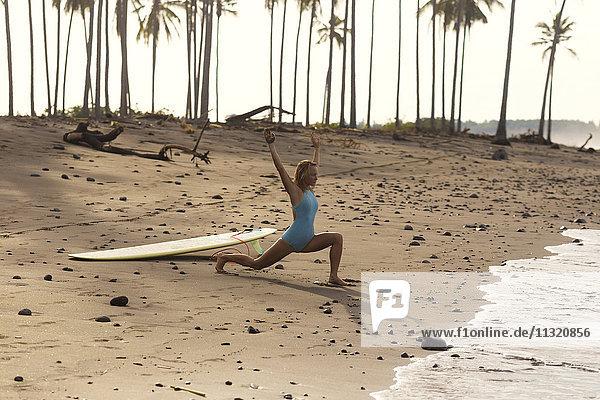 Indonesien  Bali  Frau mit Surfbrett am Strand