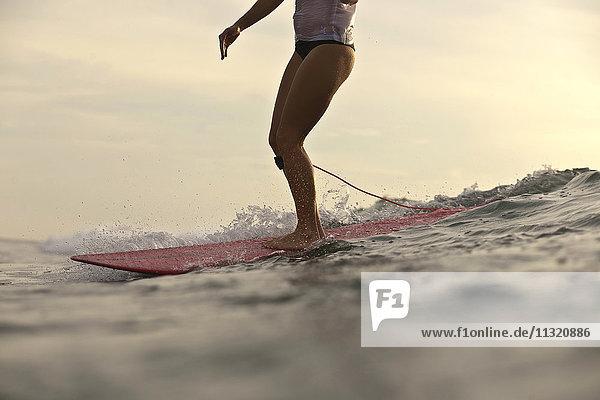 Indonesien  Bali  Frauenbeine auf dem Surfbrett