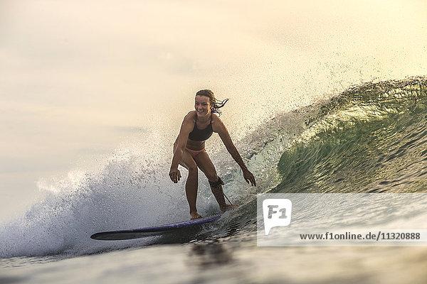 Indonesien  Bali  Frau beim Surfen bei Sonnenuntergang