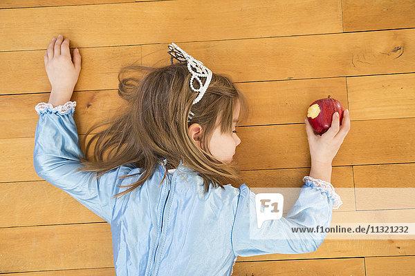 Kleines Mädchen auf Holzboden liegend mit gebissenem roten Apfel