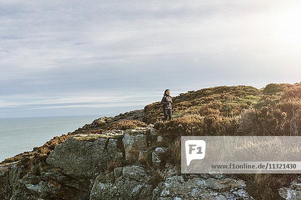Irland  Howth  Frau  die auf dem Küstenweg läuft
