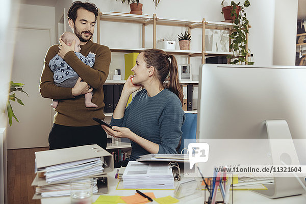 Smiling mother at desk looking at father holding baby in home office