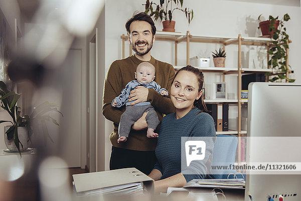 Porträt von lächelndem Vater und Mutter mit Baby im Home Office