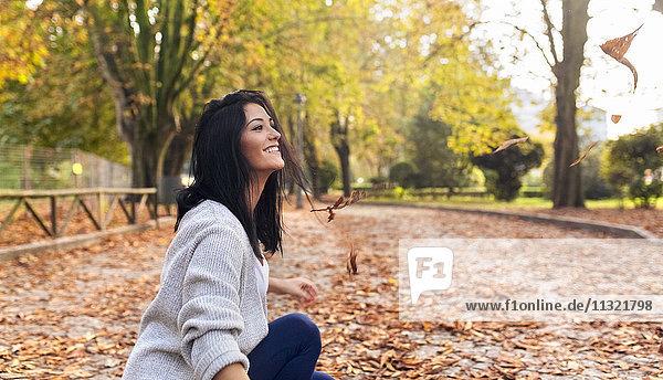 Fröhliche junge Frau spielt im Herbst mit Blättern im Park