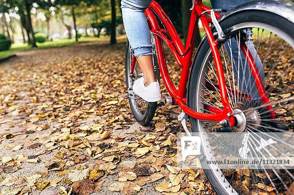 Die Beine einer Frau beim Radfahren im Herbst im Park