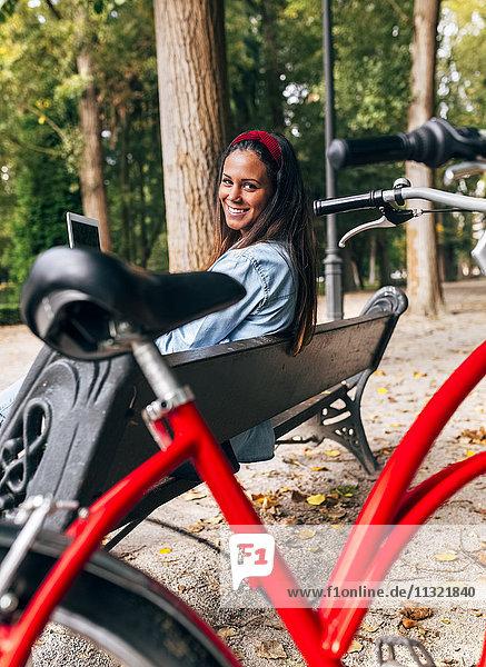 Lächelnde junge Frau sitzt auf einer Bank im Park und hält eine Tafel.