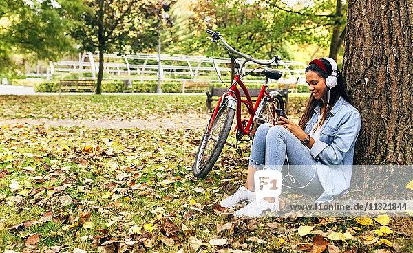 Junge Frau  die im Herbst mit ihrem Smartphone im Park Musik hört.