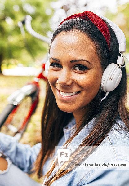 Porträt einer lächelnden jungen Frau beim Musikhören im Park