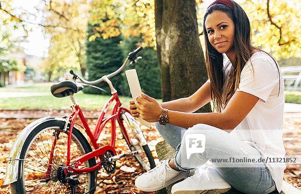 Porträt einer lächelnden jungen Frau in einem Park im Herbst mit einer Tafel
