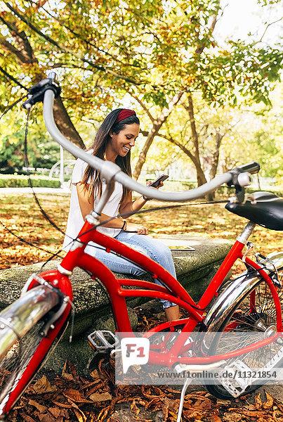 Lächelnde junge Frau schaut im Herbst auf das Handy im Park