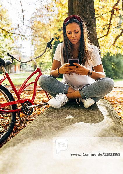 Junge Frau  die im Herbst auf dem Handy in einem Park unterwegs ist.