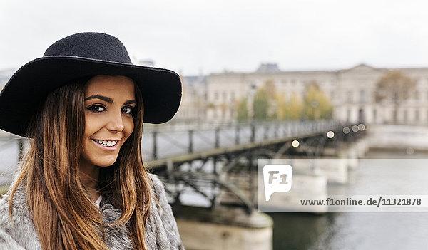 Frankreich  Paris  Porträt einer lächelnden jungen Frau mit schwarzem Hut an der Seine