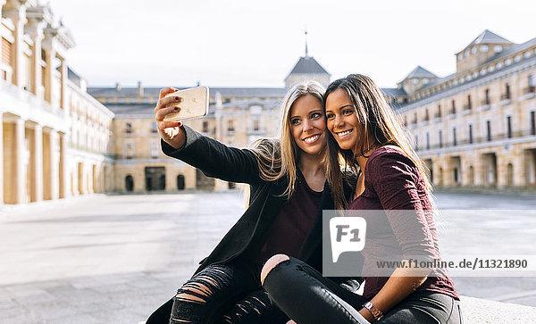 Zwei lächelnde junge Frauen auf dem Stadtplatz  die einen Selfie nehmen.