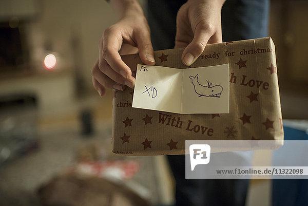 Schenken am Heiligabend  Hände halten Geschenk