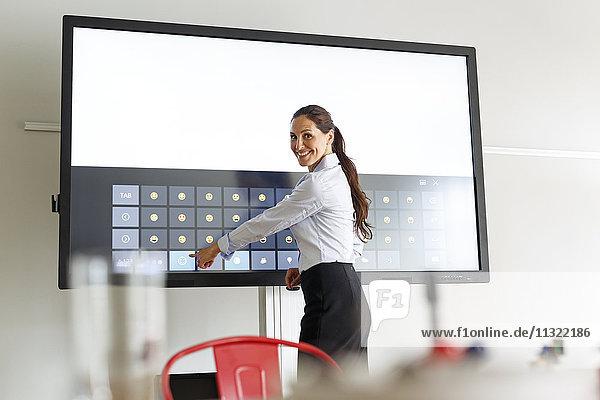 Geschäftsfrau mit Projektion einer Tastatur mit Emoticons im Konferenzraum