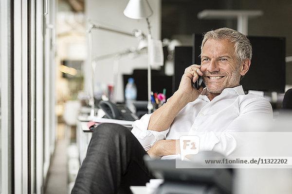 Lächelnder Geschäftsmann am Handy im Büro