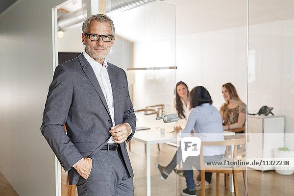 Zuversichtlicher Geschäftsmann im Büro mit Mitarbeitern im Hintergrund