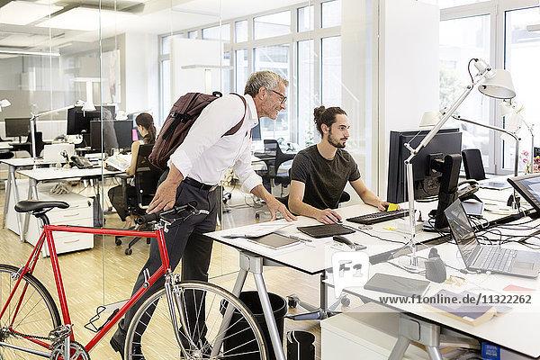 Geschäftsmann mit Fahrrad im Gespräch mit Kollegen im modernen Büro