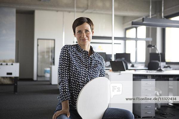 Porträt einer lächelnden Geschäftsfrau im Büro auf Stuhl sitzend