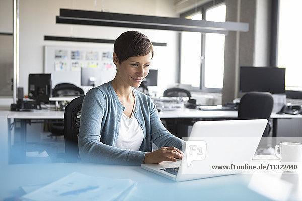 Geschäftsfrau im Büro mit Laptop