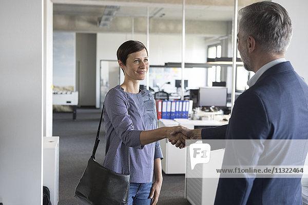 Geschäftsmann und Geschäftsfrau beim Händeschütteln im Amt