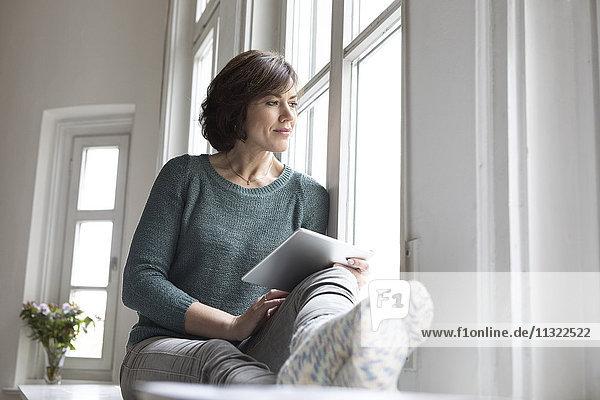 Frau mit Tablette aus dem Fenster schauend