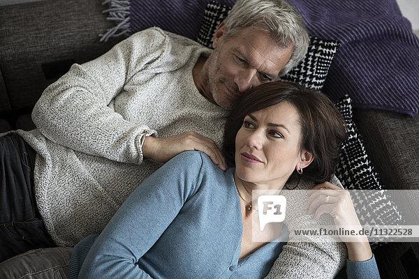 Reife Paare entspannen sich auf der Couch