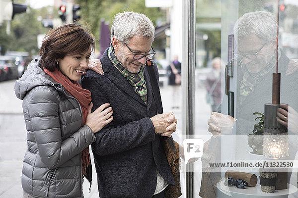 Lächelndes reifes Paar schaut ins Schaufenster