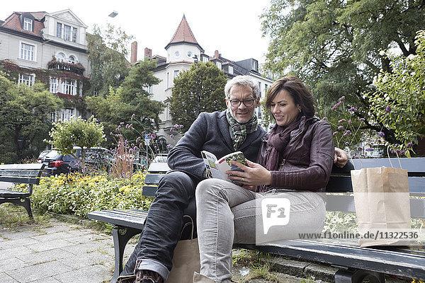 Erwachsenes Paar mit Buch auf der Bank sitzend