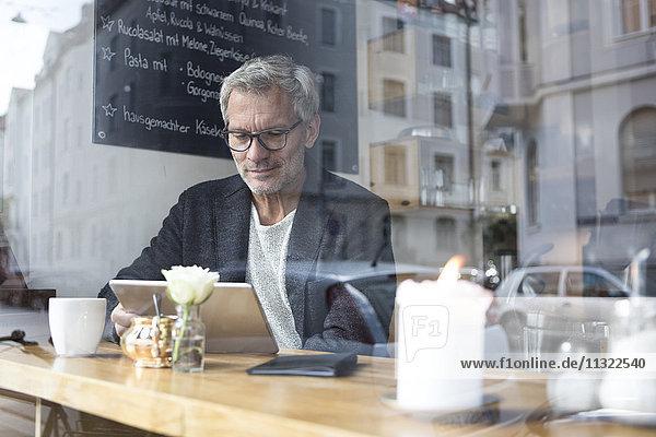 Erwachsener Mann mit Tablette im Café