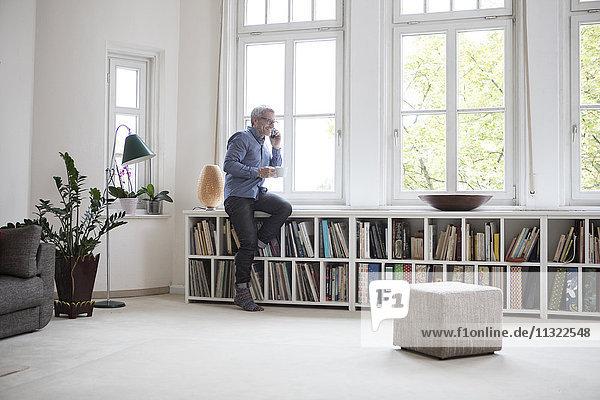 Erwachsener Mann zu Hause am Telefon