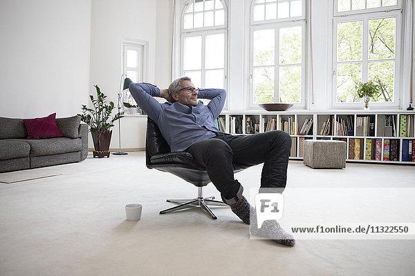 Entspannter reifer Mann zu Hause im Sessel sitzend