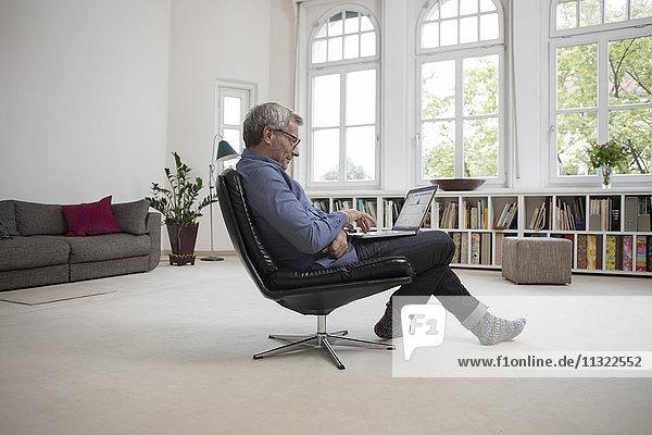 Erwachsener Mann zu Hause sitzend im Stuhl mit Laptop