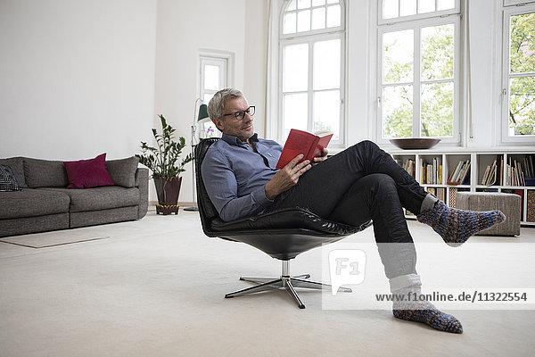 Erwachsener Mann zu Hause sitzend im Stuhl Lesebuch