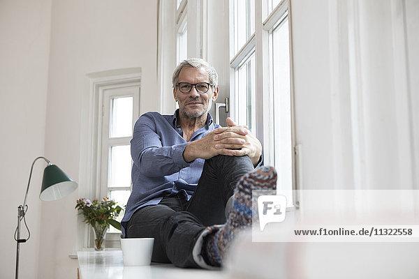 Entspannter reifer Mann zu Hause am Fenster sitzend