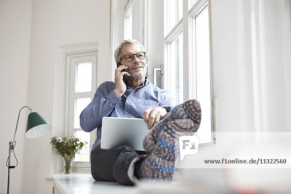 Erwachsener Mann zu Hause am Fenster sitzend mit Tablett und Handy