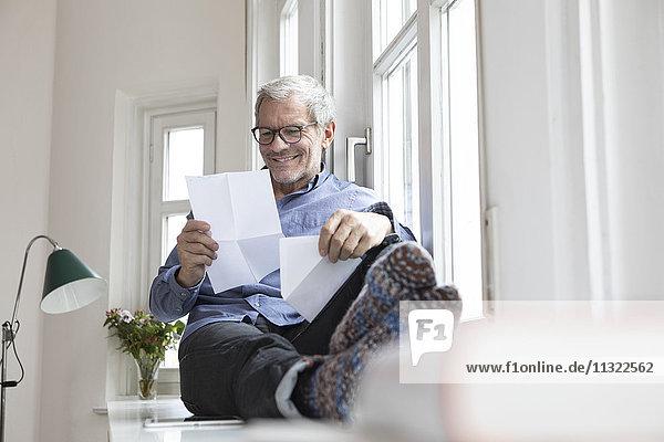 Der reife Mann zu Hause sitzt am Fenster und liest Dokumente.