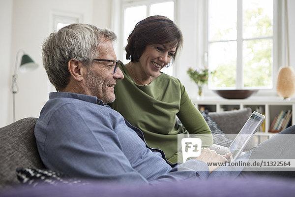 Lächelndes reifes Paar zu Hause auf dem Sofa  das sich die Tablette teilt