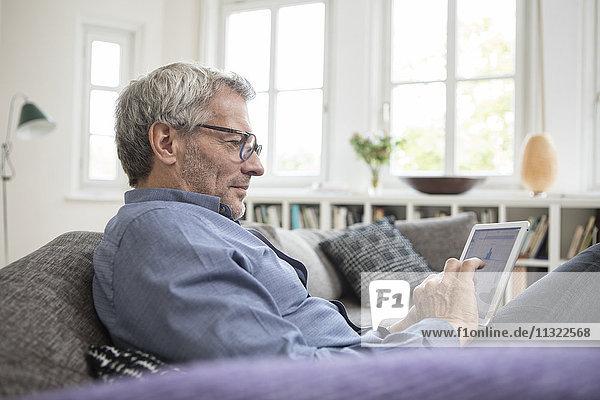 Erwachsener Mann zu Hause auf dem Sofa sitzend mit Tablette