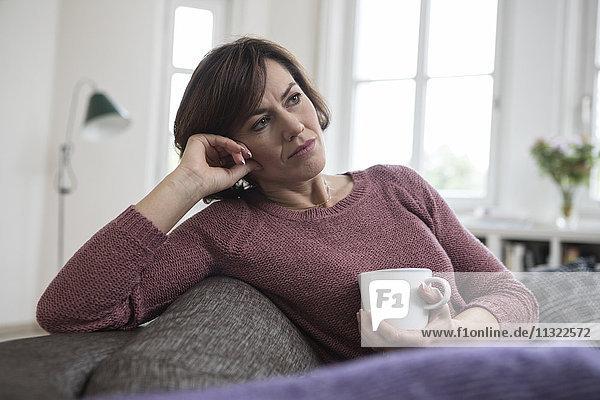 Frau zu Hause sitzend auf dem Sofa mit Tasse