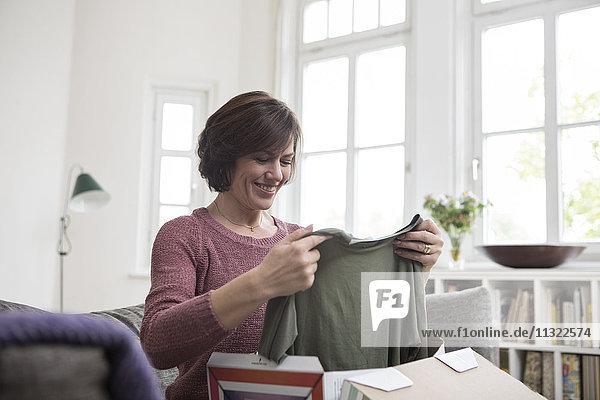 Lächelnde Frau zu Hause auf dem Sofa sitzend mit Blick auf das Kleidungsstück