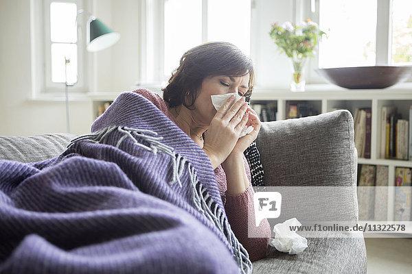 Frau mit einer Erkältung auf dem Sofa liegend