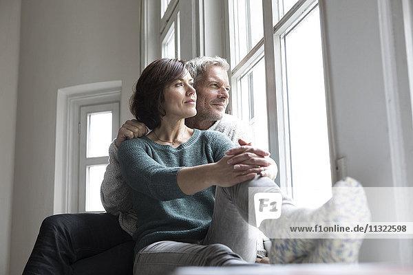 Erwachsenes Paar  das aus dem Fenster schaut