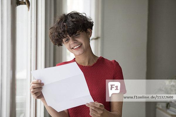 Porträt einer lächelnden jungen Frau beim Lesen eines Briefes