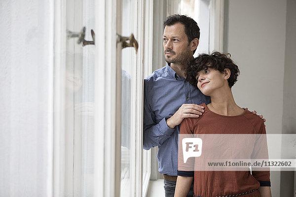 Ein Paar schaut durchs Fenster und beobachtet etwas.